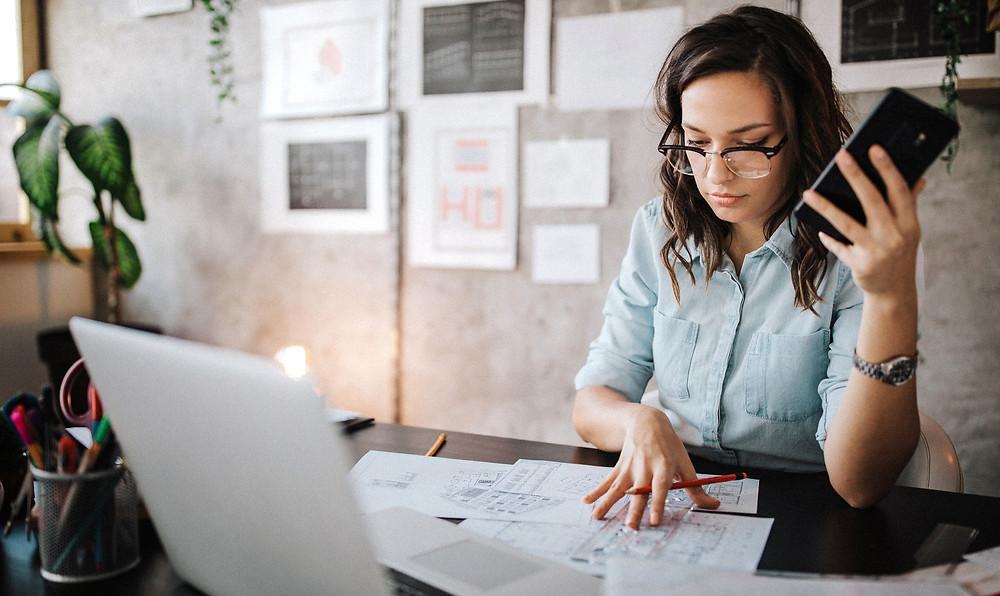 mulher de óculos sentada em frente ao computador analisando relatórios em cima da mesa e com o celular na mão