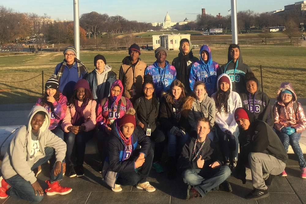 Deaf Middle School 8th graders posing for photo with the U.S. Capitol building in the background.