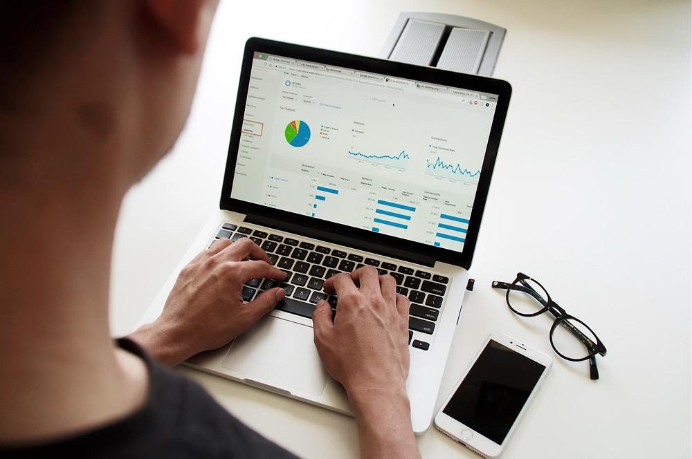 man looking at analytics charts on laptop
