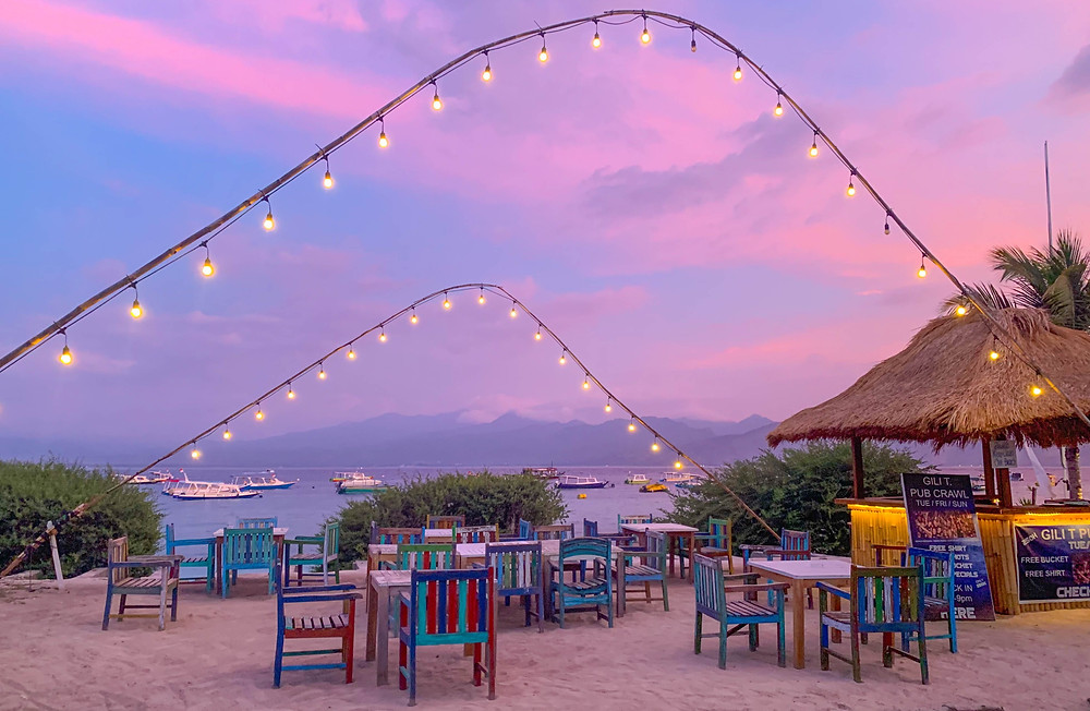 Tables, chairs, a beach bar, and hanging lights in a beach front location during a pink sunset