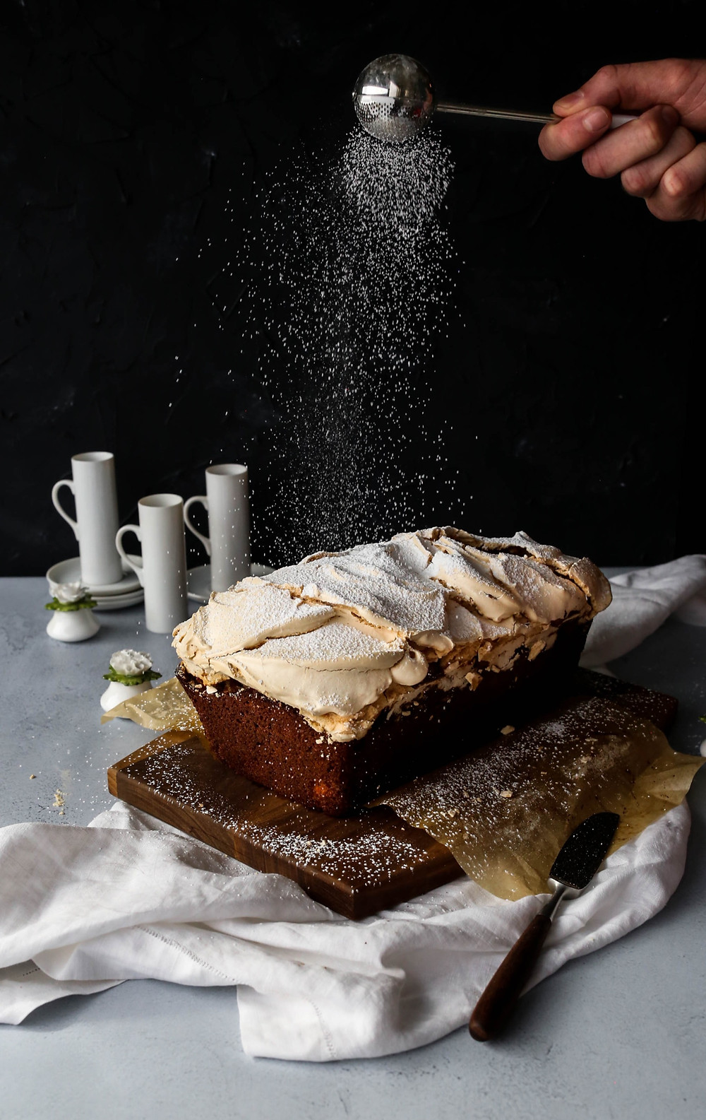 A apple and honey spiced loaf cake, topped with swirls of baked meringue. A dusting of powdered sugar is caught in mid air, floating down to coat the loaf.