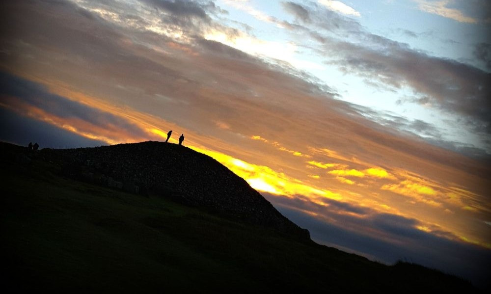 Sun rising over Loughcrew, two men silhouetted against the sky.