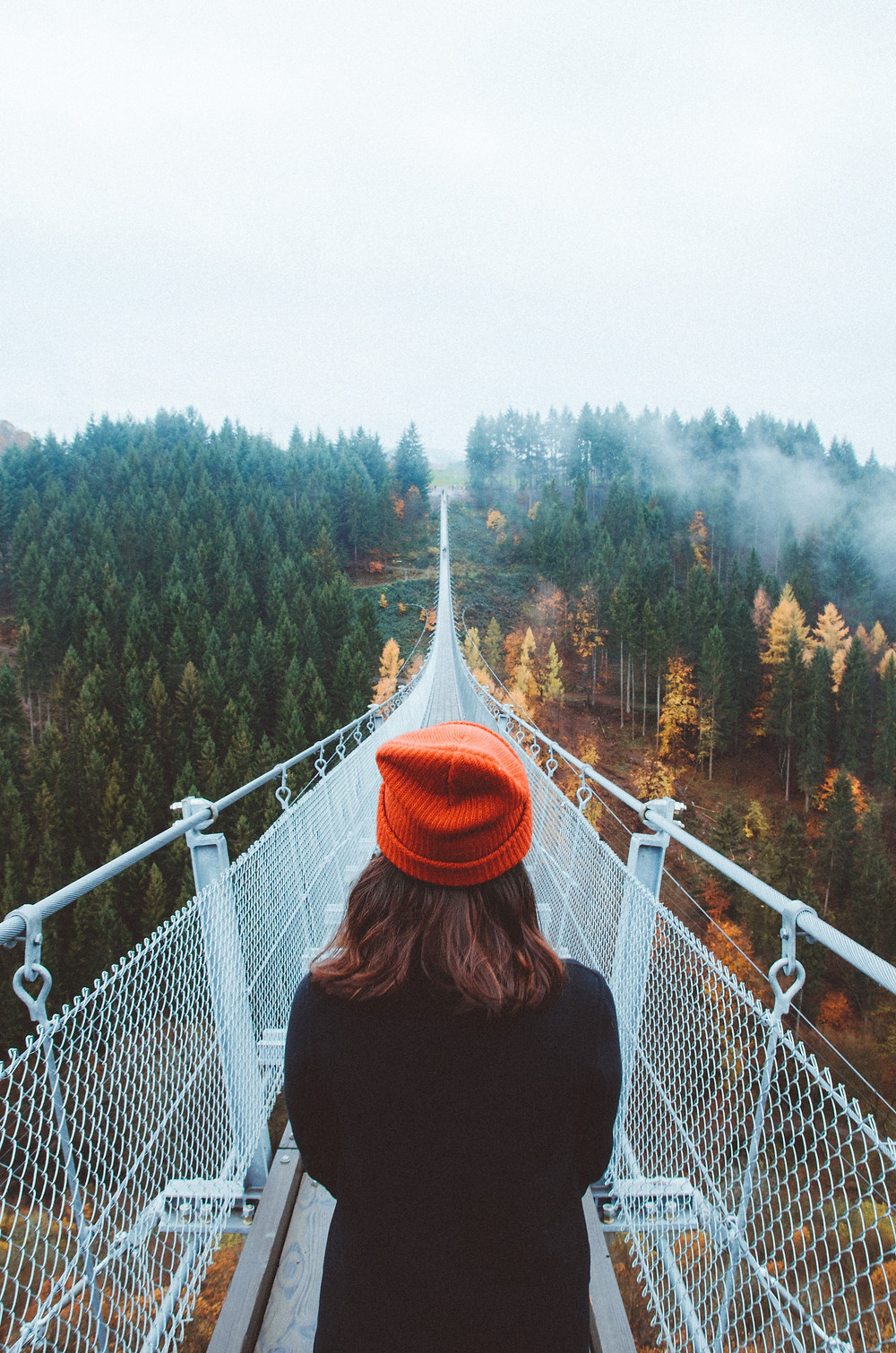 Woman in orange hat looking at a white bridge over a canyon thinking about her purpose as a caregiver in Englewood CO. We help caregivers process their grief and manage their stress in therapy at Catalyss Counseling in Denver CO 80209 and 80210