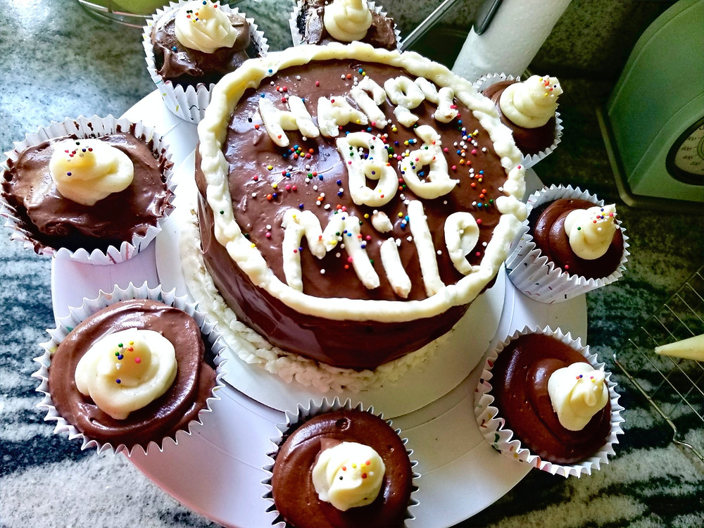 """Chocolate cake and muffins with chocolate and vanilla frosting that says """"Happy Bd Mile"""""""