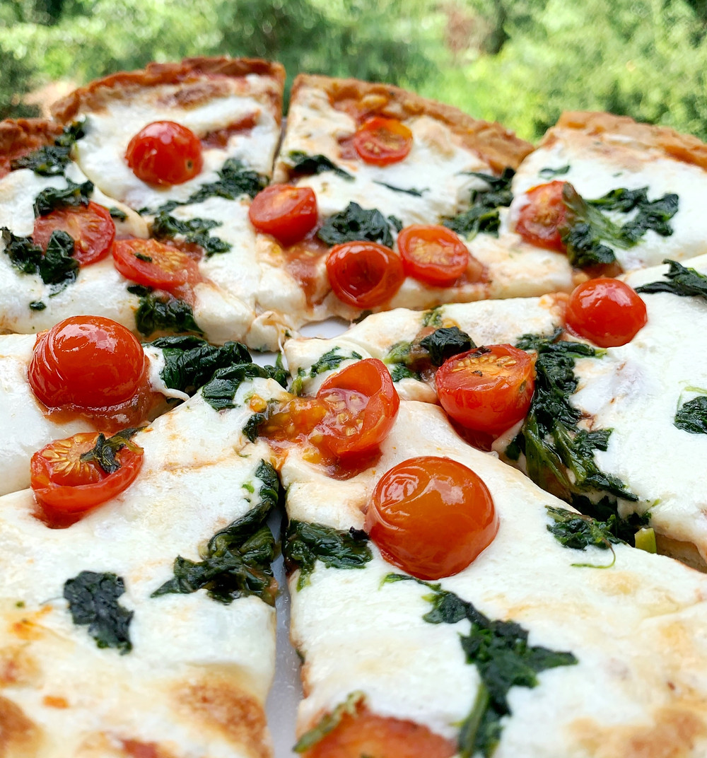 closeup surface shot of peronal pan pizza with mozzarella, cherry tomatoes, and spinach