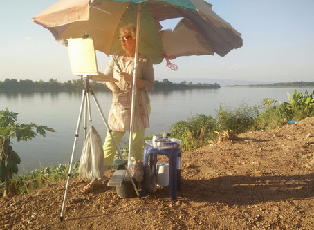 Artist in Residence painting on banks of the Mekong River