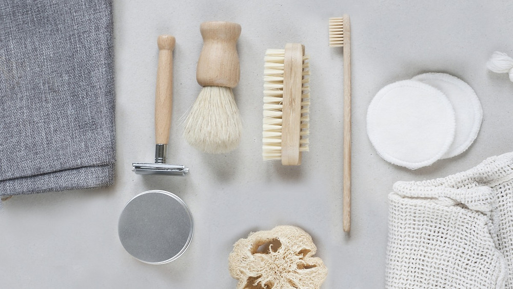 Everyday sustainable zero wastes swaps: bamboo razor, wood brush, eco-friendly toothbrush, reusable sponge, sustainable bamboo fiber pads, cotton mesh bag. Reduce your wastes easily with these swaps and tricks.