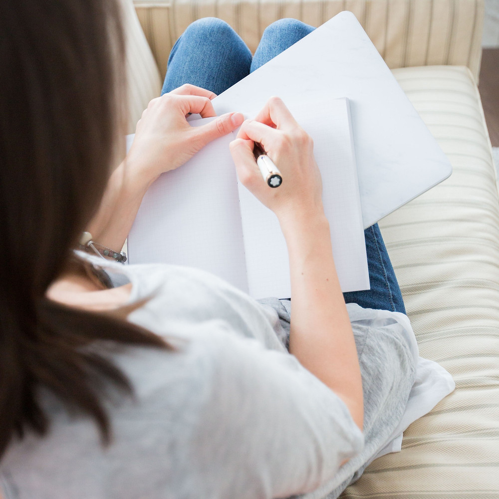 Mulher sentada no sofá, com um caderno aberto sobre o colo, segurando uma caneta com a mão direita, começando a escrever em uma folha em branco.