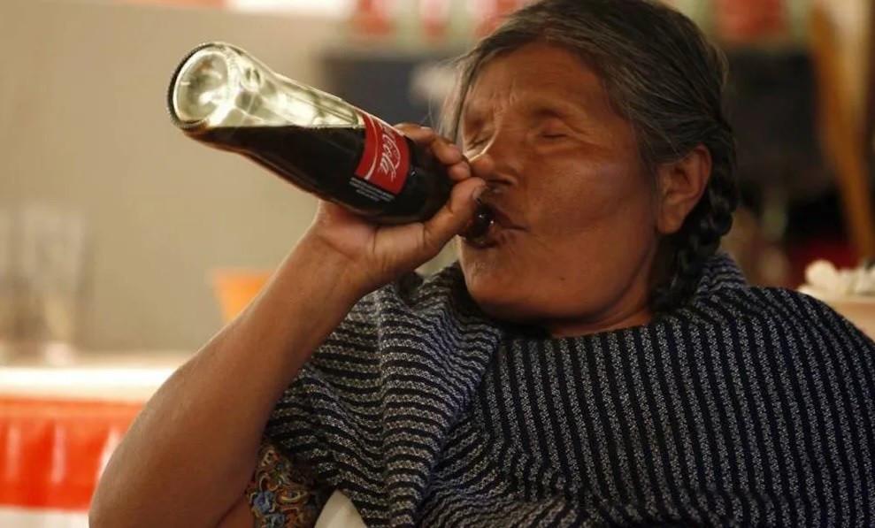 Indígena bebiendo Coca-Cola.