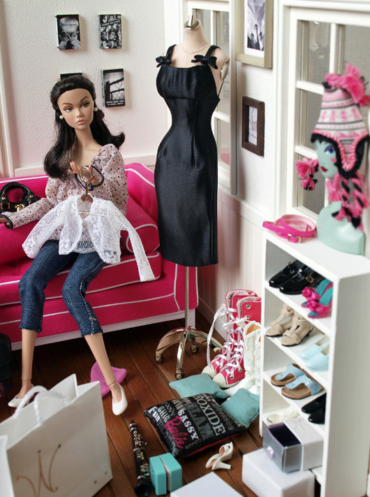 doll sat in wardrobe with clothing