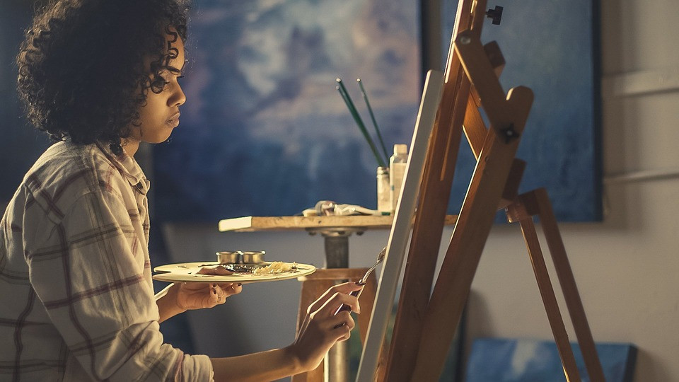 Female artist paints at an easel