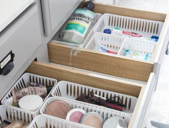 Plastic baskets with makeup and small items inside bathroom drawers