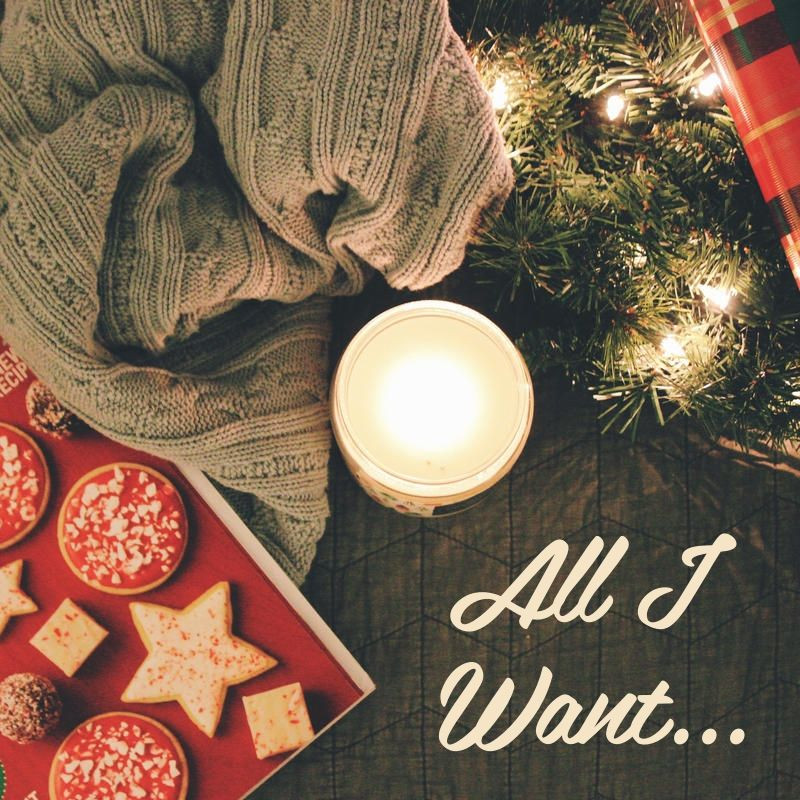 "Holiday cookies, greenery & lights surround a lit candle & a knitted blanket with the words, ""All I Want..."""