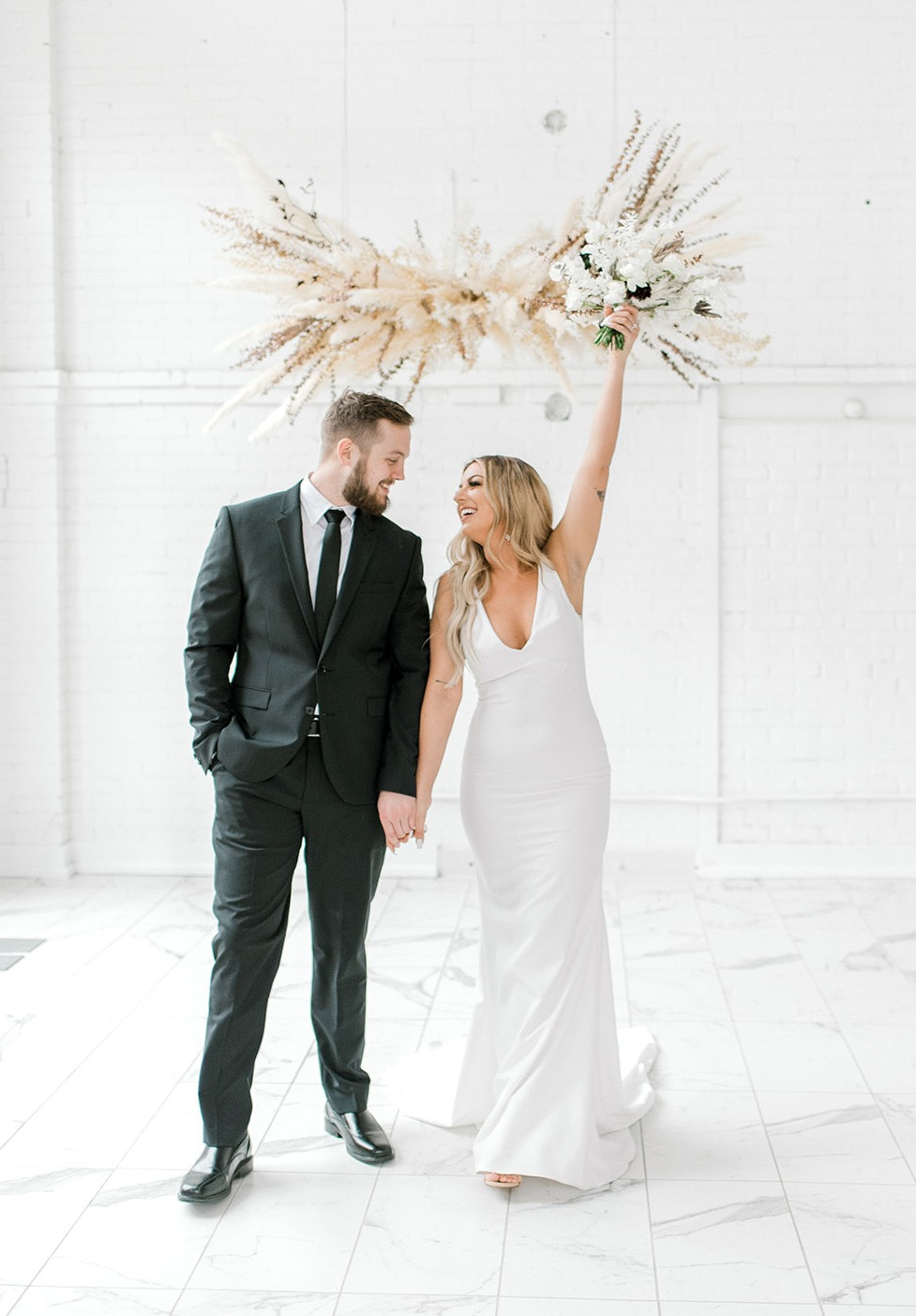 hanging pampas grass wedding ceremony arrangement by Studio Bloom Iowa with bride and groom cheering
