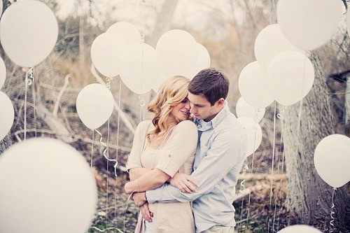 Wedding Photoshoot Props: Couple in embrace surrounded by white balloons