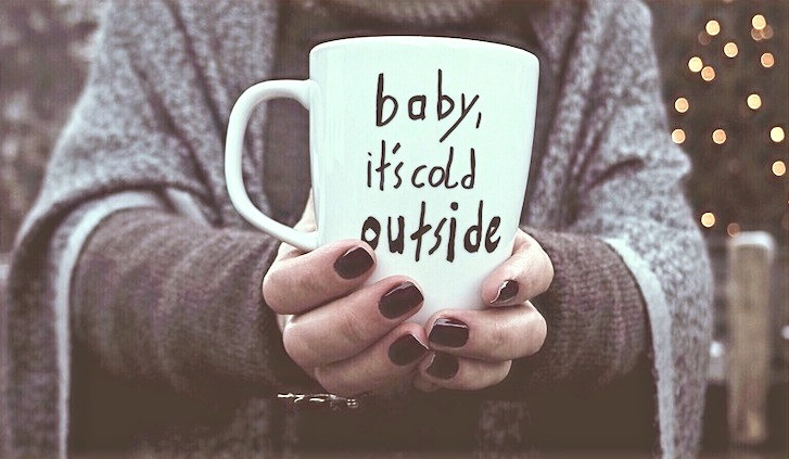 Woman-holding-a-mug-of-coco-baby-its-cold-outisde