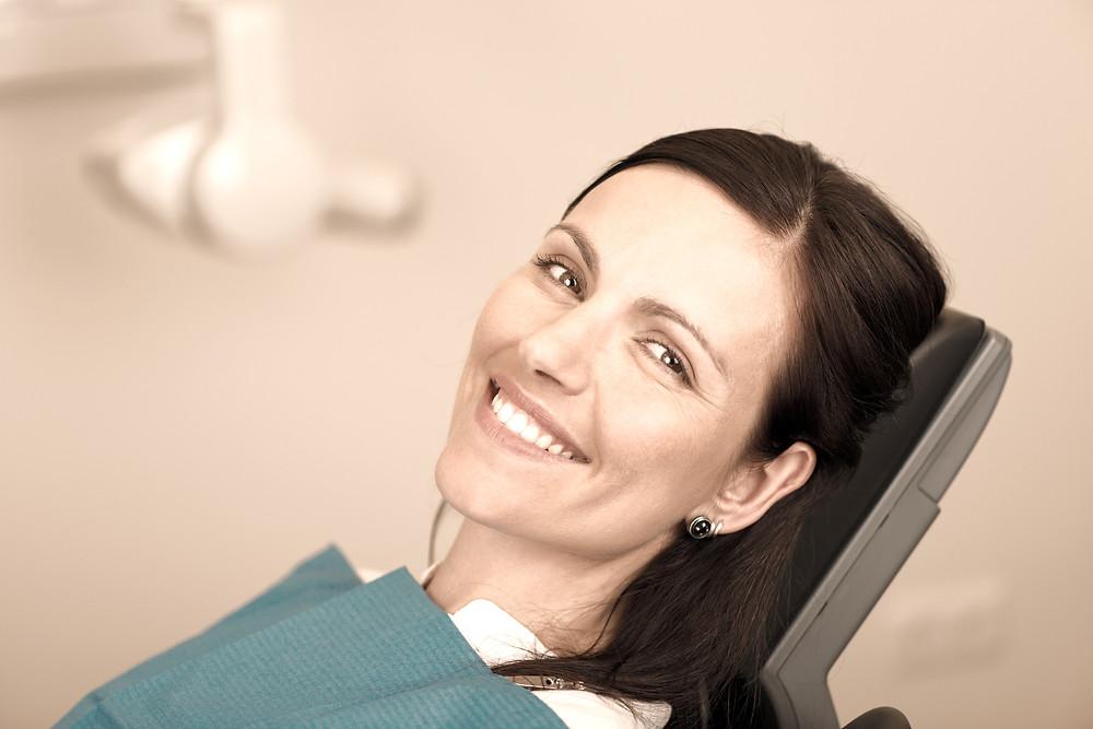 Lächelnde Frau am Zahnarztstuhl