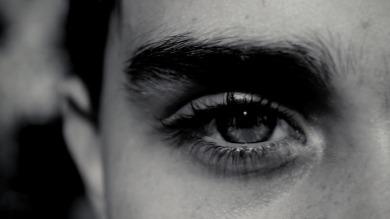 Imagem de meio rosto com um olho de homem aberto. A foto está em preto e branco.