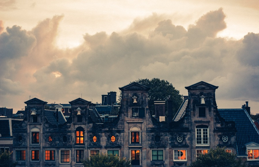 Ominous looking gothic house with orange glow from windows, cloudy with some light but no sky visible