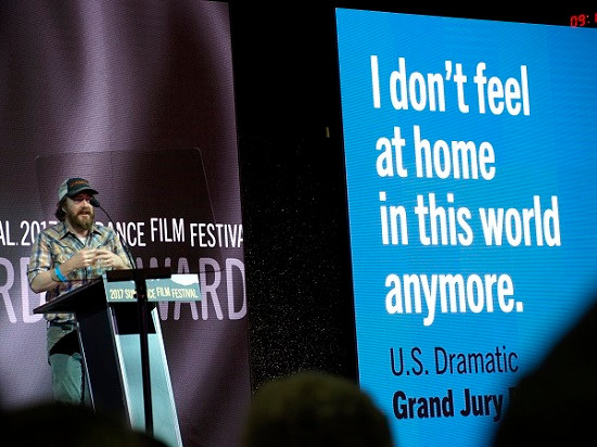 Macon Blair accepting Sundance Film Festival's Grand Jury Prize for the U.S. Dramatic category. He is a bearded man, wearing a short-sleeves short and a baseball cap.