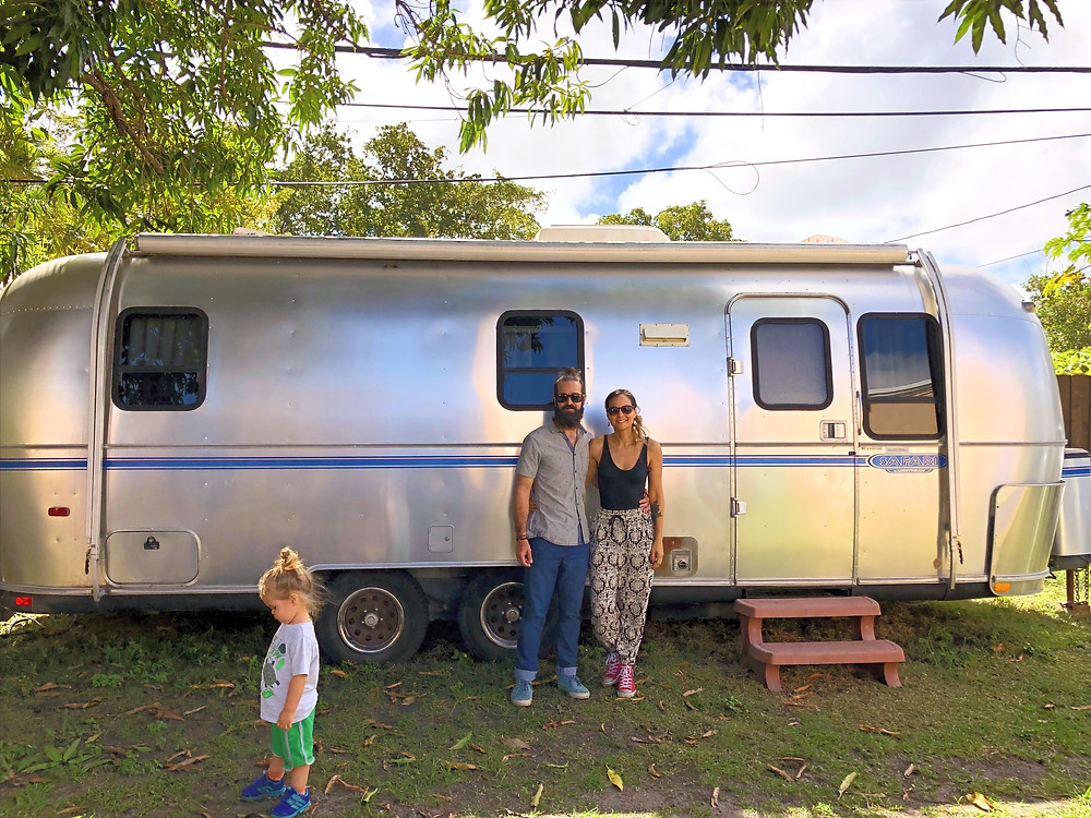 Couple standing in front of an airstream travel trailer