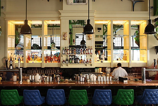 John Dory Oyster Bar, blue and green bar stools, New York Bar, black pendant lights, bar design, mirrored bar, glass shelving, Oyster Bar, bar counter, bar display, bar shelving,