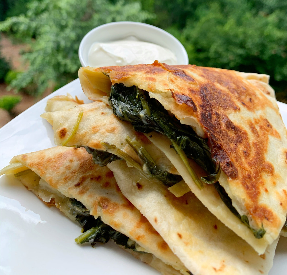 spinach and artichoke quesadillas stacked on top of each other with sour cream in ramekin on the side on a white plate