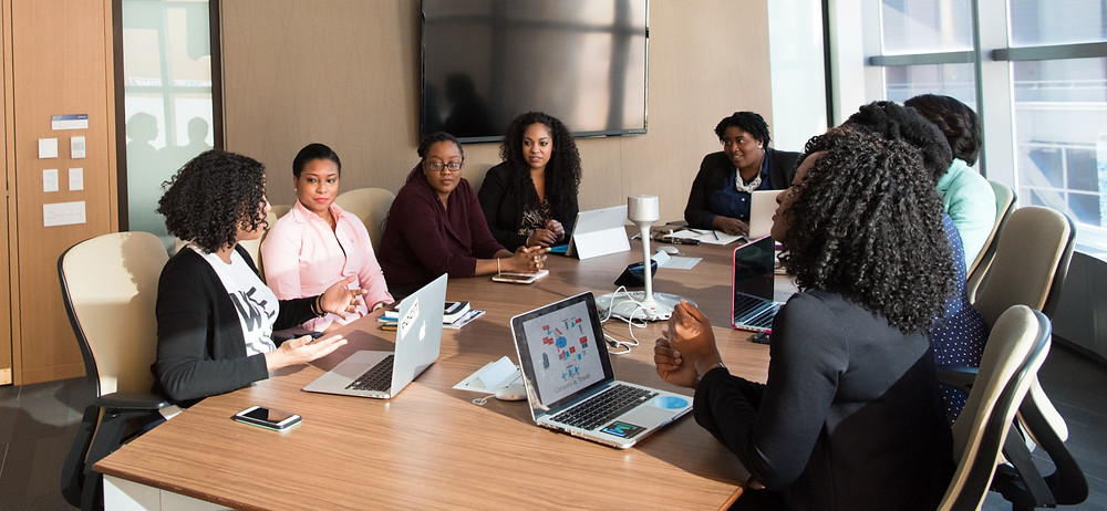 Professional Black women around a conference room table