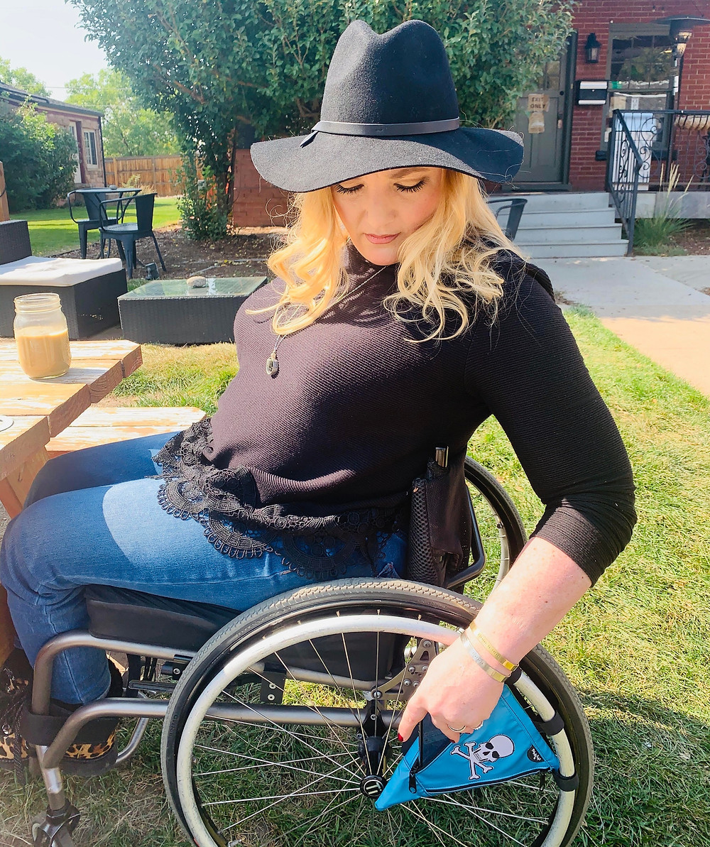 Kate Nelson, is a beautiful white female with blonde hair past her shoulders. She is wearing a black sweater with black lace detail along the bottom and jeans. She is also wearing a fall suede hat. She is using our electric blue with skull patch pie bag that is attached to the spokes of her wheelchair, she is putting her cellphone inside the bag with just one-hand.