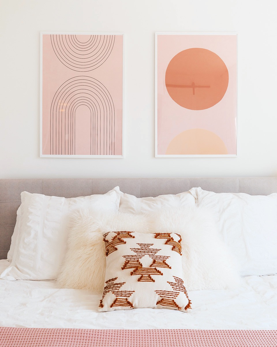 Two blush midcentury prints framed and hung above a bed with white blankets.