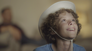 A film still from short film Showdown showing a boy looking off smiling whilst wearing a white hat.