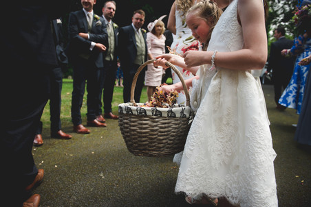 Flower girls carrying around large basket of flower petal confetti