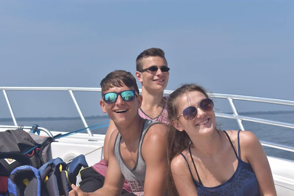 Siblings having fun on a boat