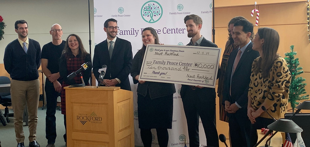 Members of the Next Rockford Strategy Team present a check to Mayor Tom McNamara for the benefit of the Family Peace Center