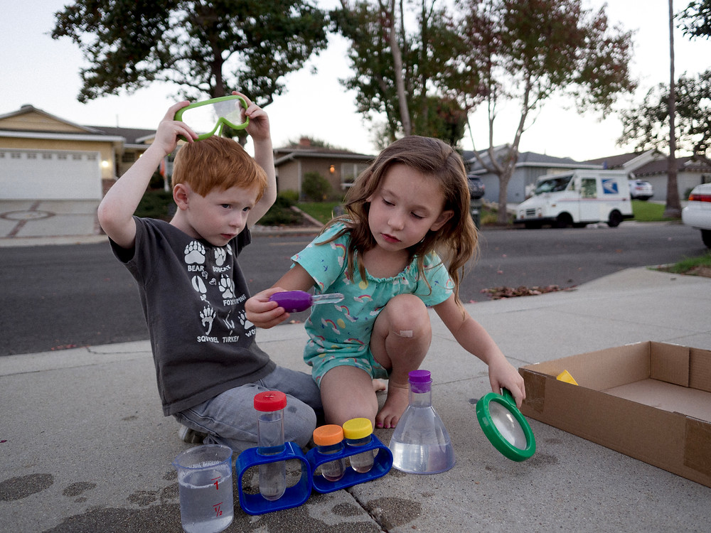 "Young boy and girl playing with their ""chemistry"" set on the sidewalk"