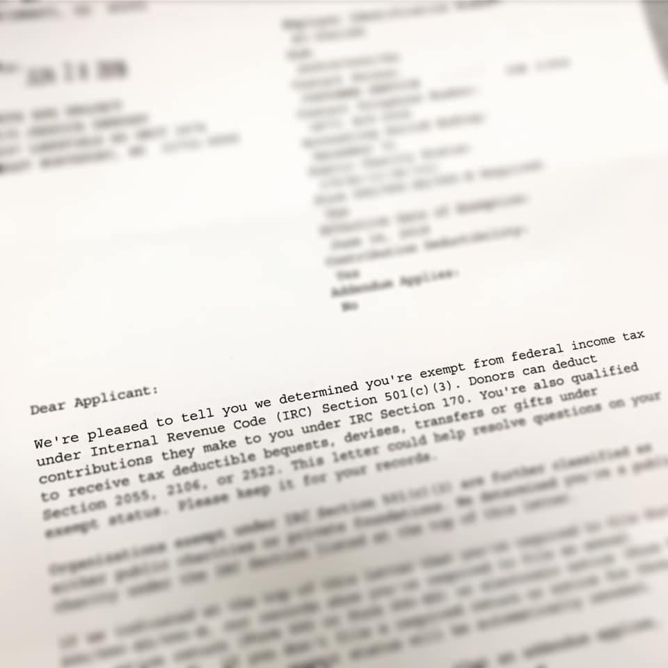 A close up of a letter with lots of text but only a small portion in focus: dear applicant: we're pleased to tell you we determined you're exempt from federal income tax under internal revenue code section 501c3. Donors can deduct contributions they make to you under IRC section 170.
