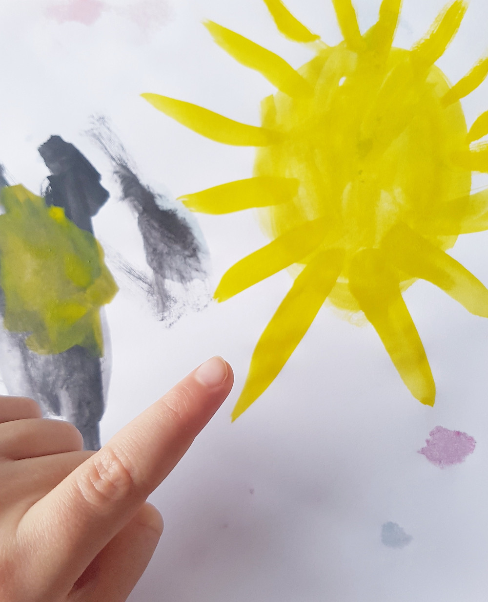 Child pointing at painting of sun