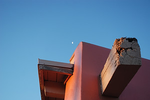 The corner of an adobe style picnic pavilion is highlighted by early morning light with the moon still showing in the sky above.