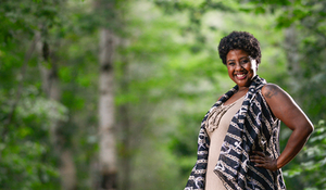 proud black woman standing in wooded forest, with a big smile.