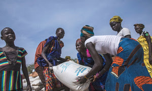 Sudanese women carrying a sack of food obtained via humanitarian aid.