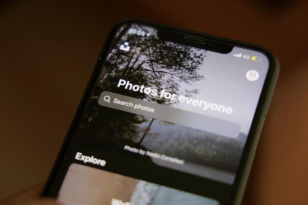 Masanın üzerinde Unsplash uygulaması açık olan bir iPhone