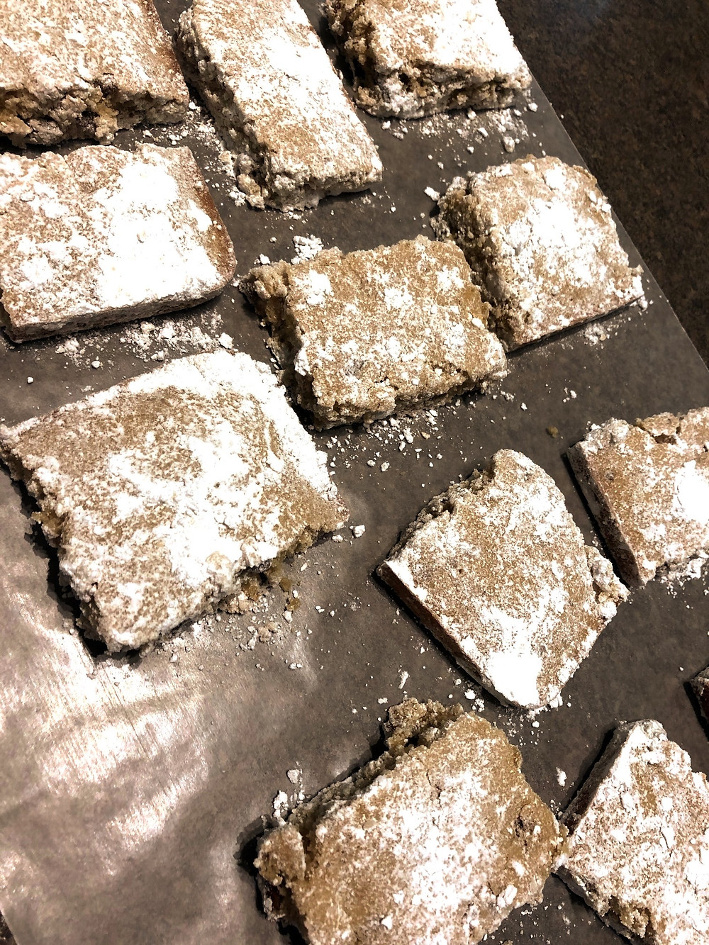 Rows of cookie-like bars sit on wax paper and are coated with white powdered sugar.