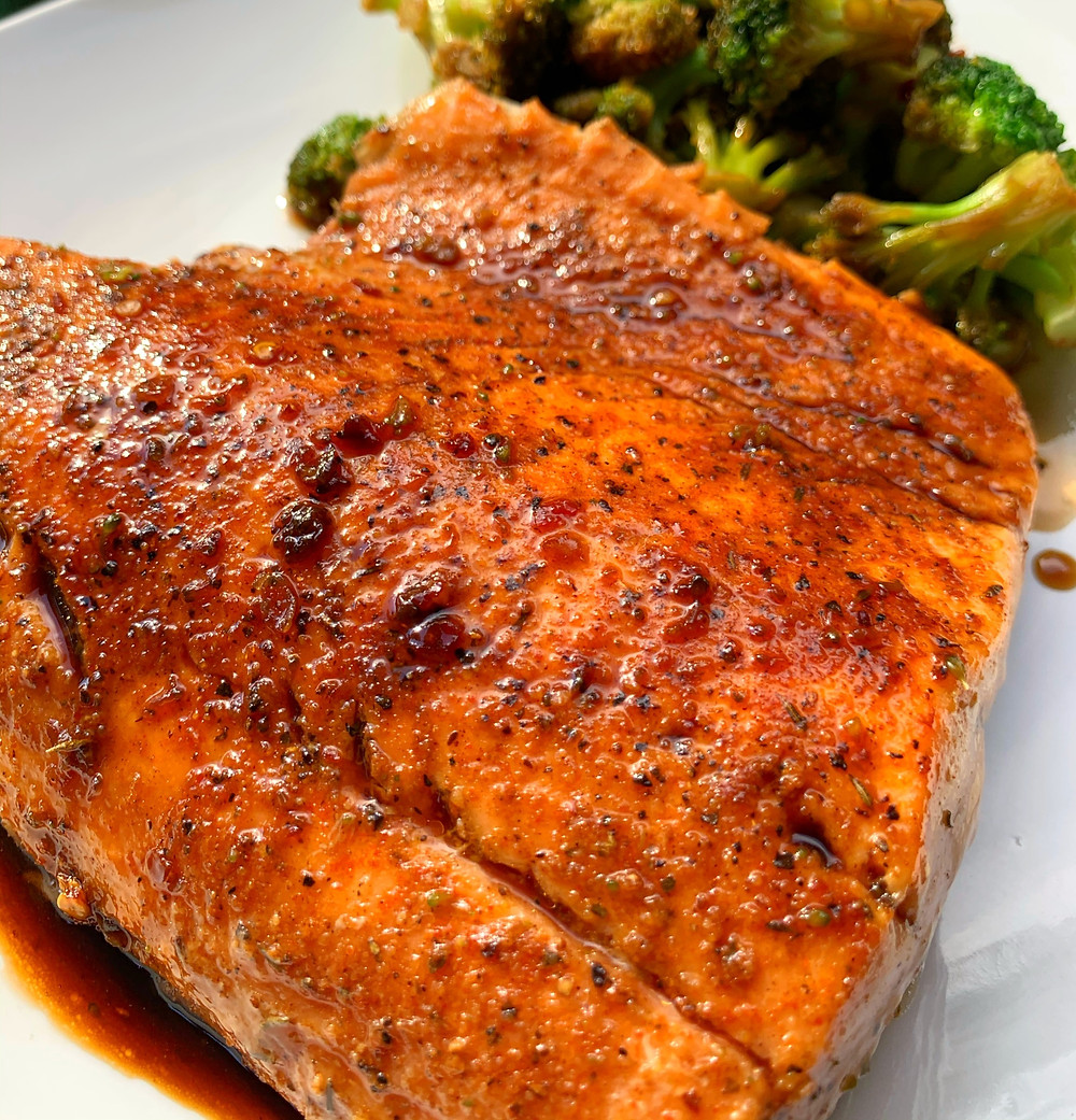 closeup shot of garlic honey soy glazed salmon with seared broccoli in the back