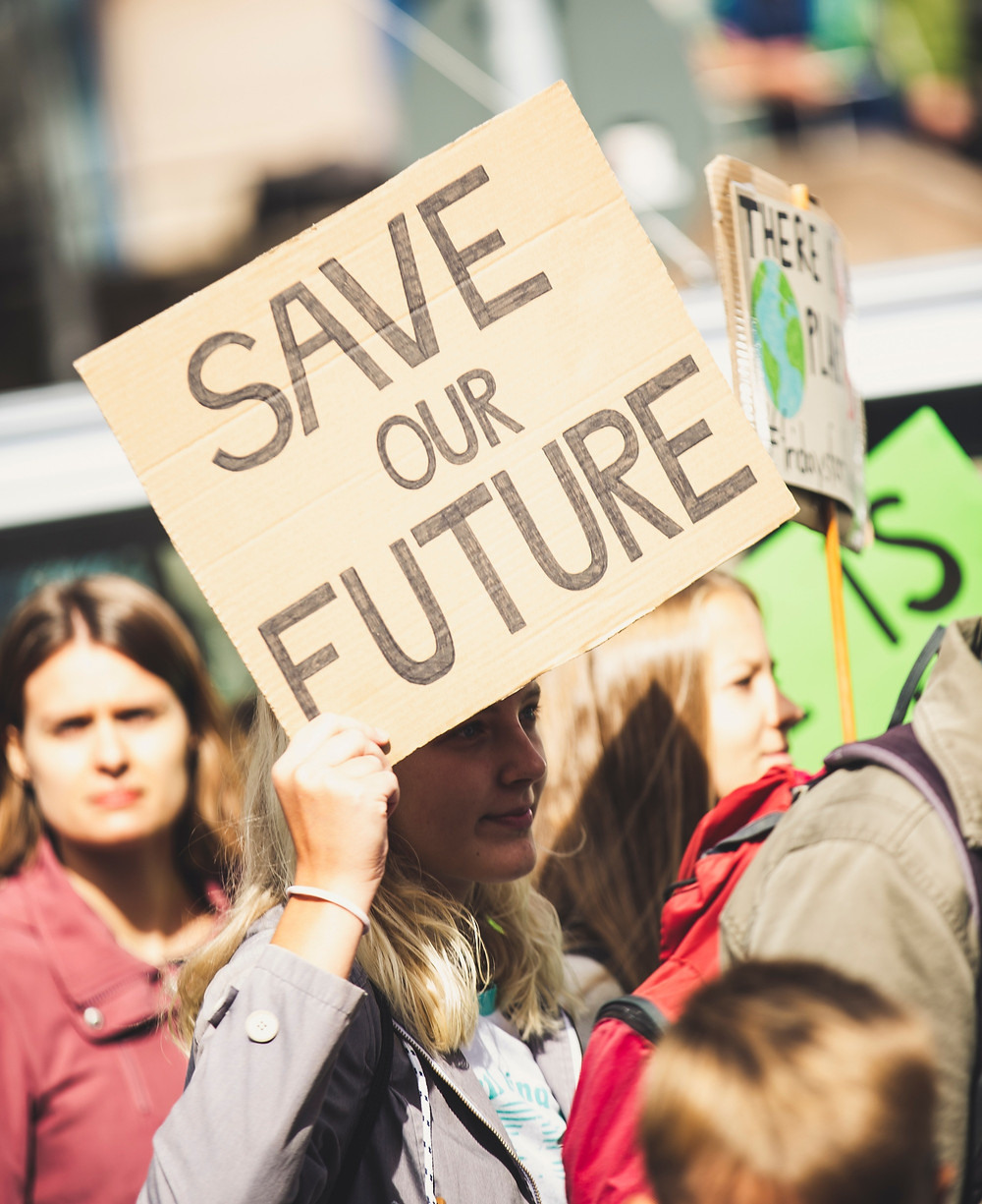 """Woman holding sign """"save our future."""""""