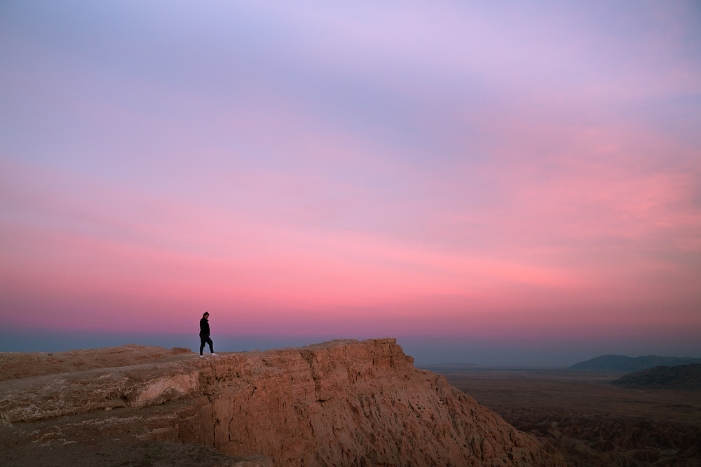 hiker standing on the ledge of a cliff under a colorful sunset
