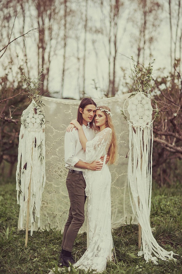 Wedding Photoshoot Props: Couple in embrace with a macrame dream catcher backdrop in the woods