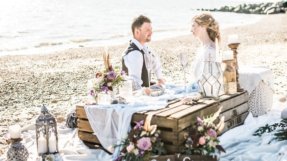 Bride and groom have informal beach picnic wedding ceremony with crate table and lanterns