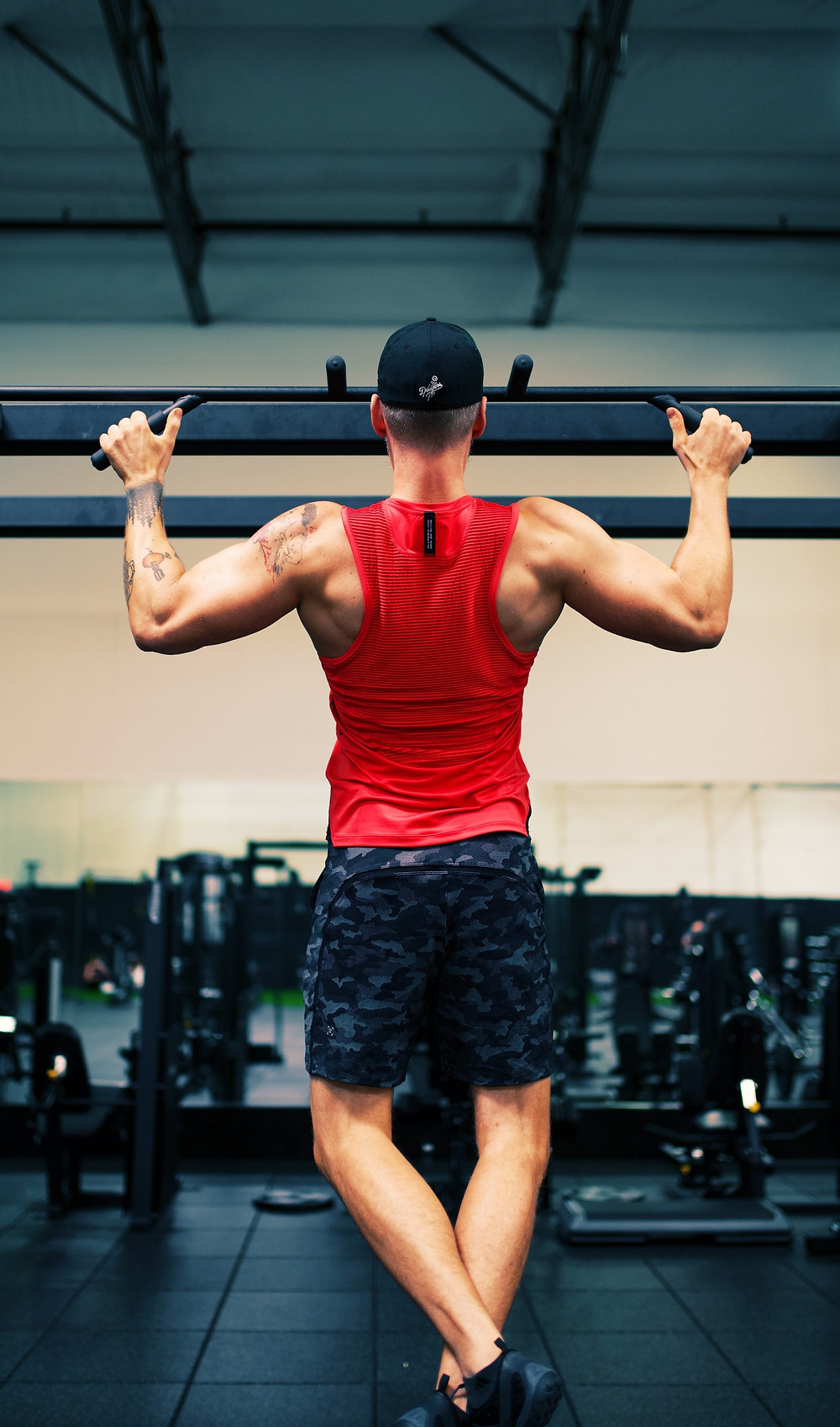 Man in Red top doing a Pull-up with a depressed and retracted scapular position.