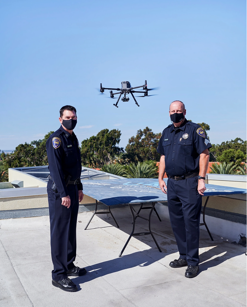 Two California police officers standing next to drone being use with artificial intelligence.