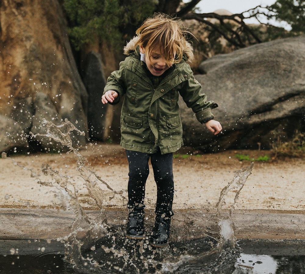 ילד קופץ בשלולית ונהנה מהחוויה